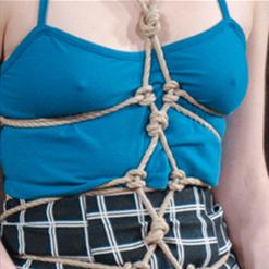 Aria Alexander bent forward in clam tie rope bondage