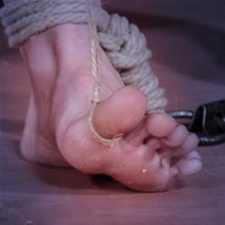 Billy Nyx balanced on ankle rope bondage
