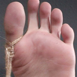 Roxanne Rae's wrists tied in rope bondage