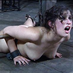 Marina wrists locked to metal chastity belt.