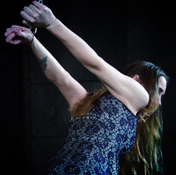 Metal cables around her wrists keep Sierra Cirque bound
