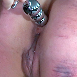 Milcah Halili bent over in metal bondage, ass in the air