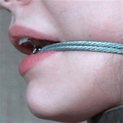 Charlotte Sartre stood up in belt and metal bondage
