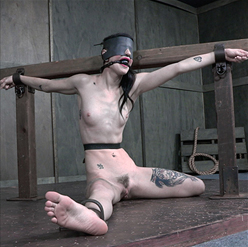 Lydia Black made up like porcelain doll in rope and gag