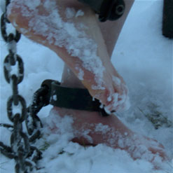 Sierra Cirque is barefoot in snow, ankles shackled