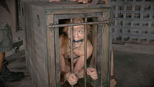 Gagged Darling watches the action in a cage