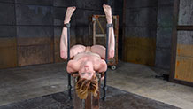 Kay Kardia on back, legs spread in metal bondage