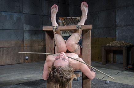 Mercy West wooden bondage, on back, legs in stocks