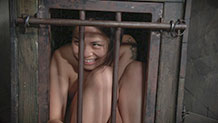 Milcah Halili giggles from inside her cage