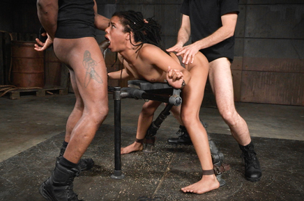 Shackled slave girl Kira Noir stuffed from both ends by cock